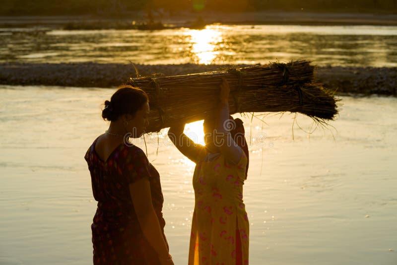 De Dorpsbewoners van Nepal oogsten Bundel Straw Carrying Head royalty-vrije stock foto's