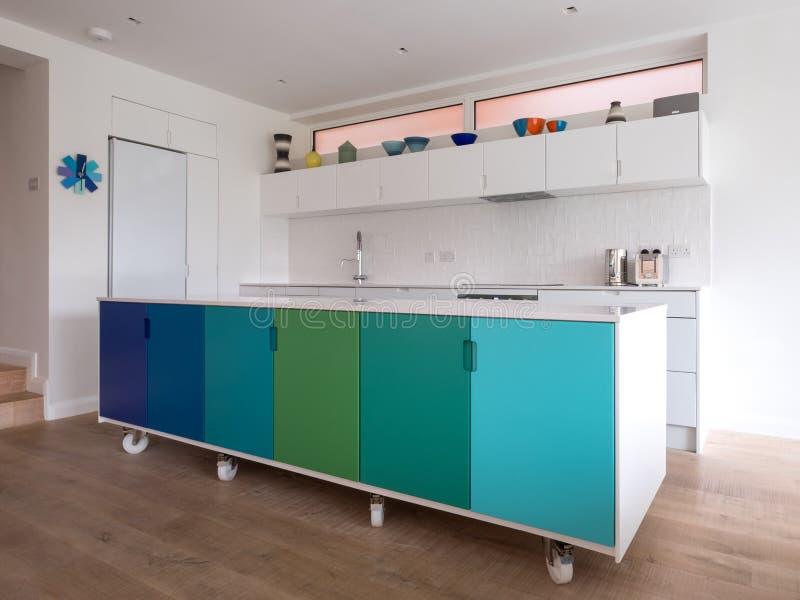 De douane ontwierp keukeneiland in open plankeuken op industriële die beverwielen, retro ontwerp in blauwe en groene kleuren word stock afbeelding