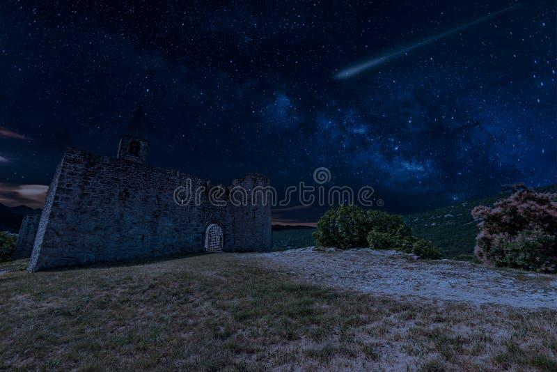 De Douche van de Perseidmeteoor over Drievuldigheidskerk in Hrastovlje, Slovenië stock foto