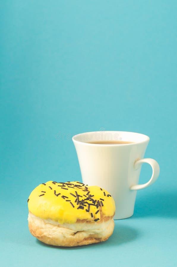 de doughnut en coffe vormt ge?soleerd op blauwe achtergrond/Doughnut in gele glans en witte coffekop op blauwe achtergrond tot ee stock foto