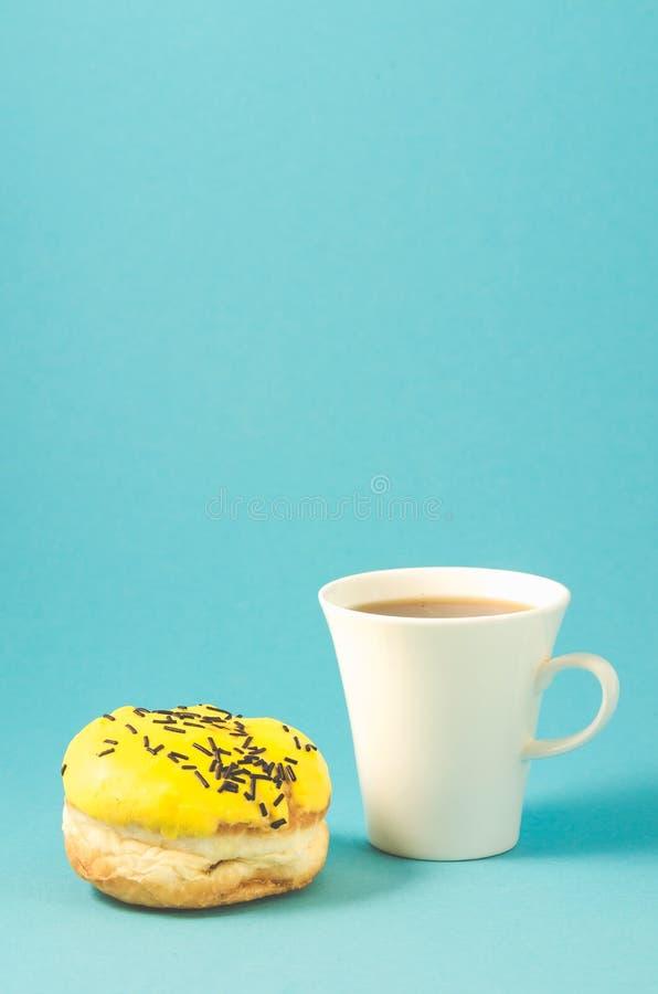 De doughnut en coffe vormt op blauwe achtergrond/Doughnut in geel glansdec tot een kom stock afbeeldingen