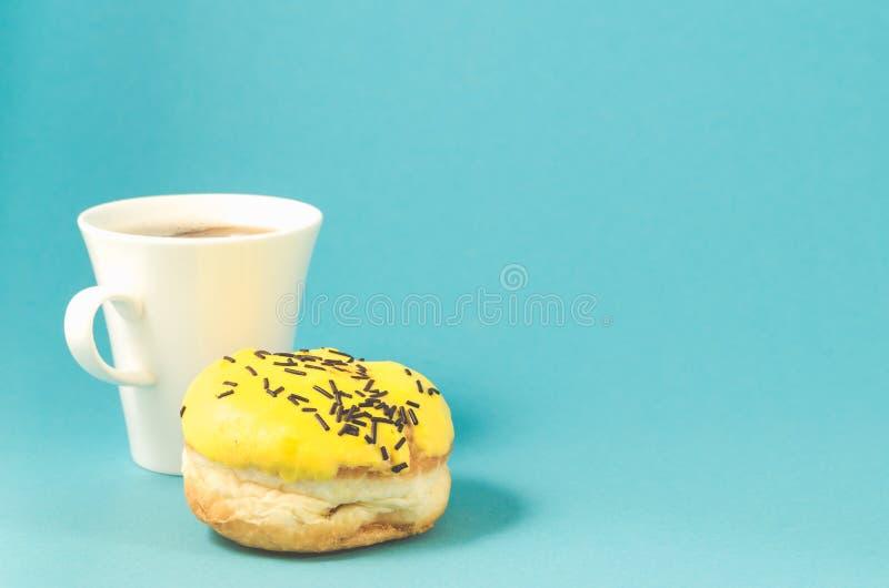 De doughnut in gele glans en coffe kop op blauwe achtergrond/de Doughnut in gele glans en coffe vormt op blauwe achtergrond, exem stock fotografie