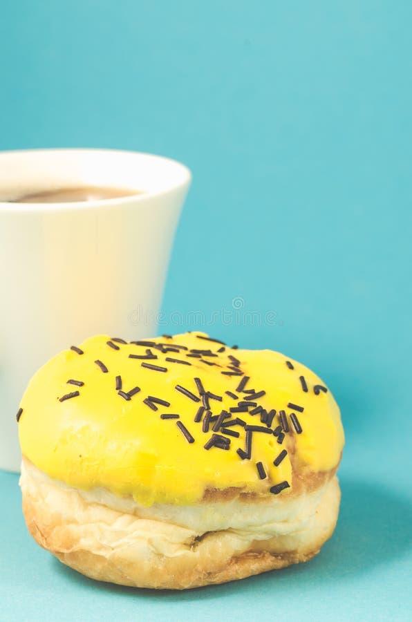 De doughnut in gele glans en coffe vormt binnen op blauwe achtergrond/Doughnut tot een kom royalty-vrije stock foto's