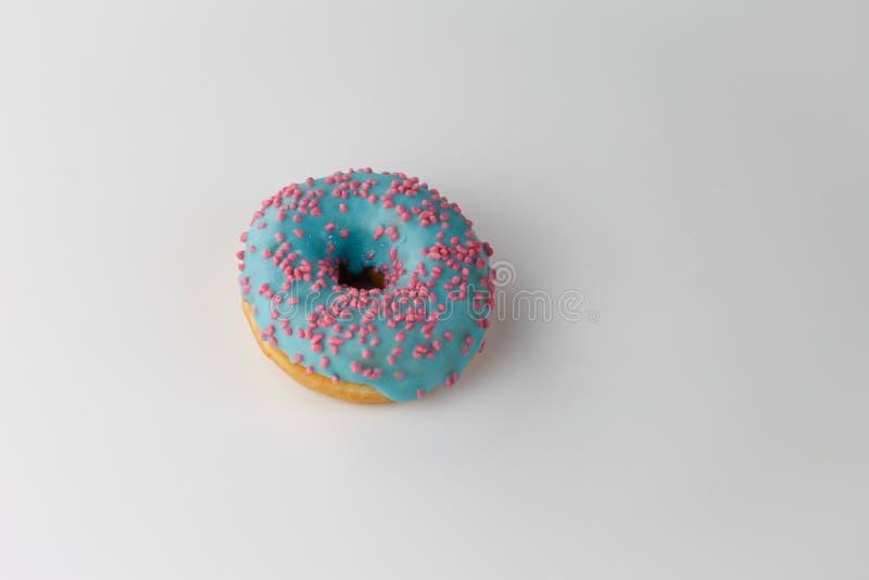 De doughnut met blauwe glans en roze bestrooit op witte achtergrond Hoogste mening stock afbeelding