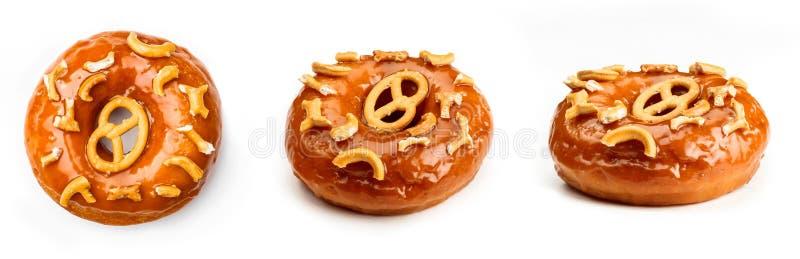 De doughnut verglaasde met karamel en stukken van pretzel, op witte achtergrond wordt geïsoleerd die royalty-vrije stock afbeelding