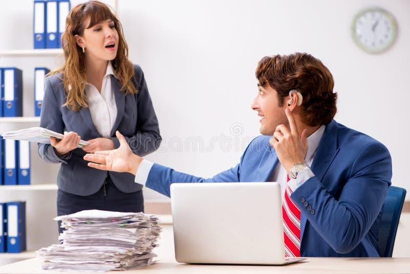 De dove werknemer die gehoorapparaat gebruiken die aan werkgever spreken royalty-vrije stock afbeeldingen