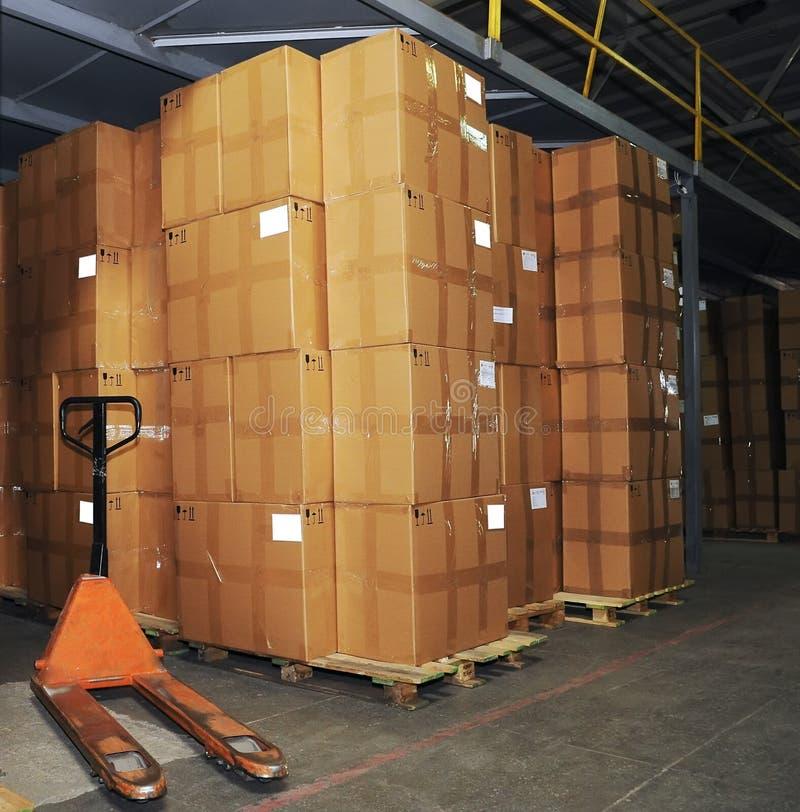 De dozen van Catron en palletvrachtwagen in pakhuis royalty-vrije stock afbeeldingen