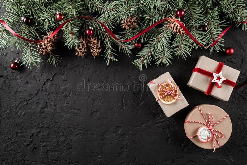 De dozen van de Kerstmisgift op donkere vakantieachtergrond met Spar vertakt zich, denneappels, rode decoratie royalty-vrije stock afbeeldingen