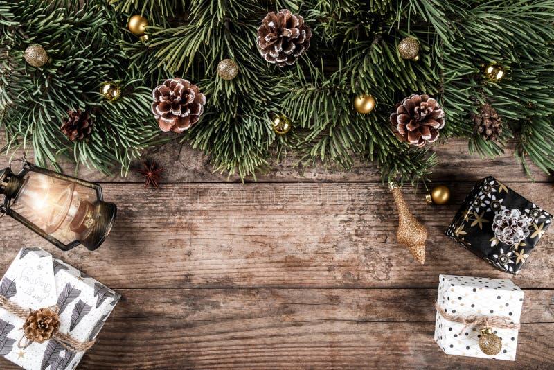 De dozen van de Kerstmisgift op vakantie houten achtergrond met spar vertakt zich, lamp, denneappels, rode decoratie stock afbeelding