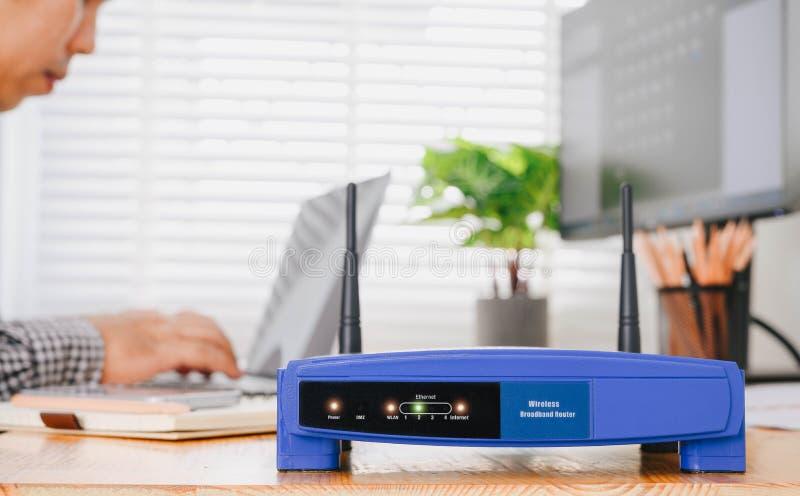 De draadloze router en de mens die laptop in bureau gebruiken draadloos breedband thuis laptop computer telefoongesprek wifi conc royalty-vrije stock afbeeldingen
