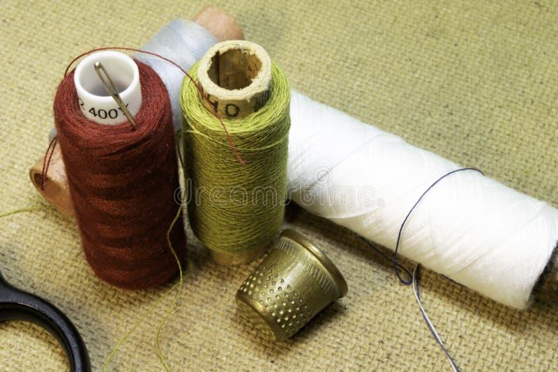 De draden, de naalden, het vingerhoedje en de schaar zijn op de lijst stock foto