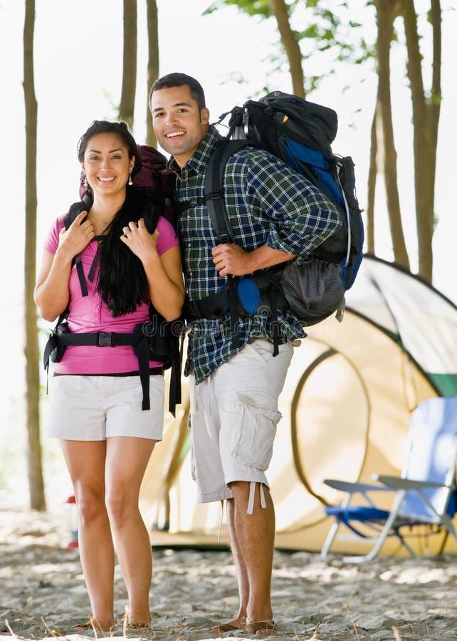 De dragende rugzakken van het paar bij kampeerterrein stock afbeelding