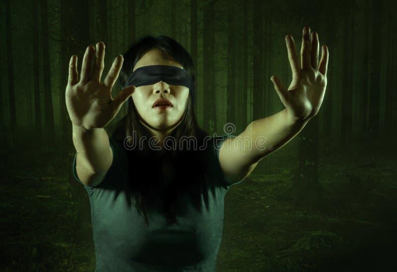 De dramatische samenstelling van jongelui deed schrikken en blinddocht Aziatisch Koreaans die tienermeisje in het donkere bos ver royalty-vrije stock afbeelding