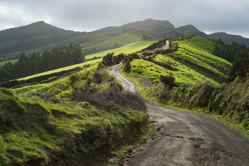 De dramatische windende sleep van de wegweg in het landschap van het grasgebieden van bergenweiden, Nieuw Zeeland royalty-vrije stock foto's