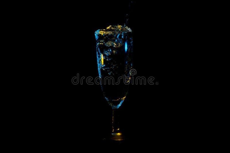 De drank die over de bovenkant van een glas borrelen benadrukte in geel en blauw en geïsoleerd op een zwarte achtergrond royalty-vrije stock foto's
