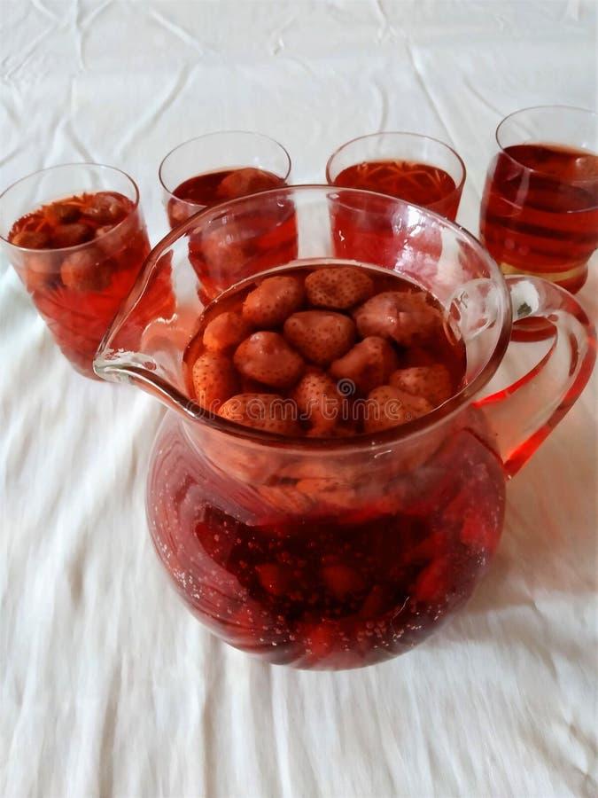 de drank met natuurlijke bessen van aardbei, heldere rode smakelijke kleur, het is nuttig, vitaminen het in een glas wordt gegote stock foto