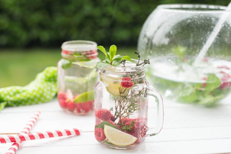 De drank van de de zomerverfrissing Water met framboos, kalk, ijs en munt op rustieke achtergrond royalty-vrije stock afbeelding