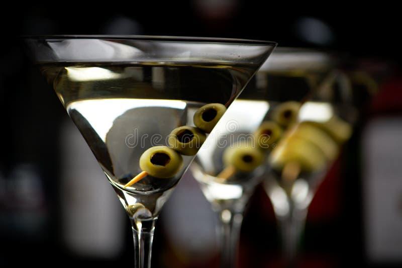 De dranken van close-upmartini met stok in bar op zwarte stock foto's