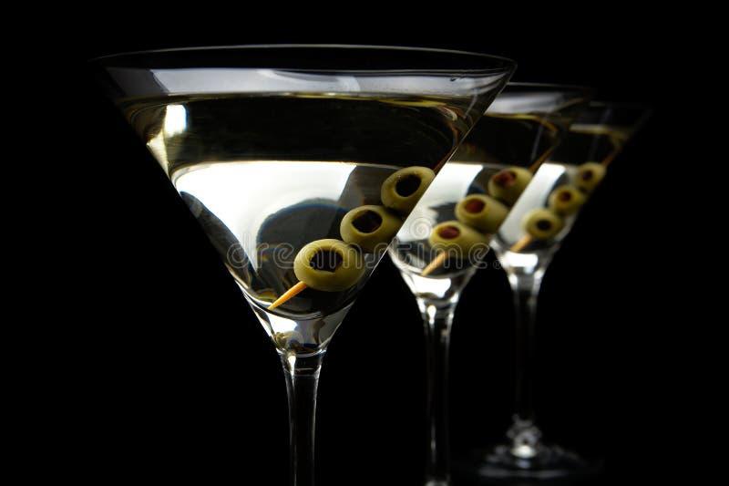 De dranken van close-upmartini met stok met olijven op zwarte stock fotografie