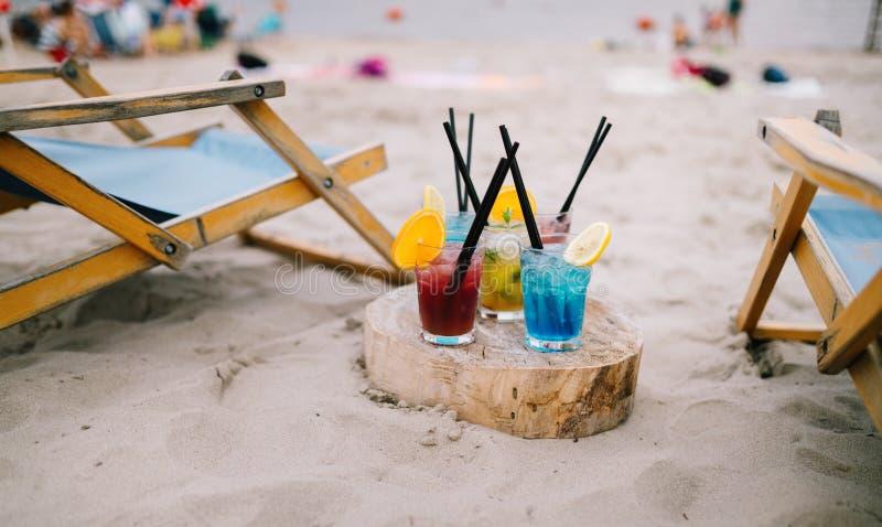 De dranken van de zomer met onduidelijk beeldstrand op achtergrond Het concept van de vakantie stock foto