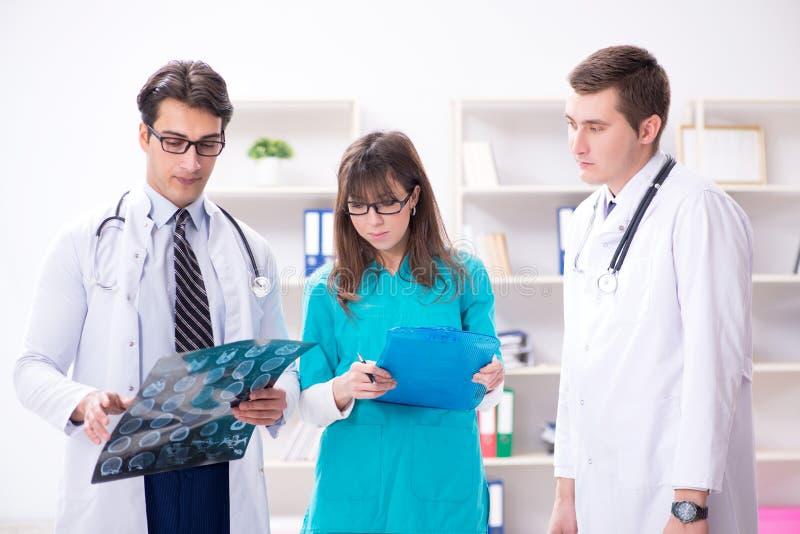 De drie artsen die aftastenresultaten van x-ray beeld bespreken royalty-vrije stock afbeelding
