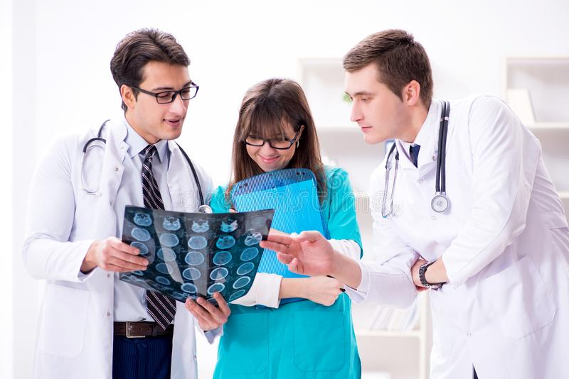 De drie artsen die aftastenresultaten van x-ray beeld bespreken stock foto's