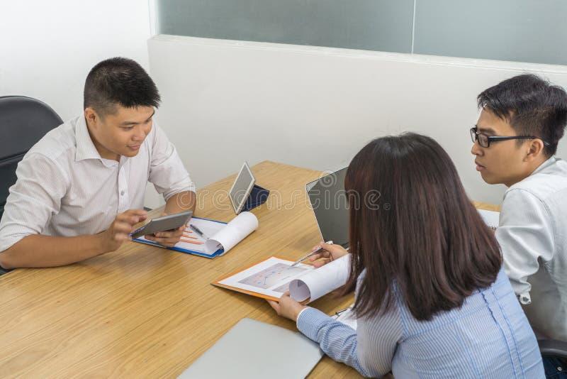 De drie bedrijfswerknemer bespreekt over financieel document stock foto's