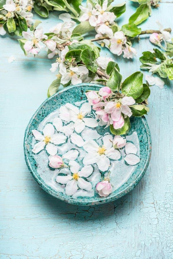 De drijvende bloesembloemen met groene bladeren in Turkoois blauw water werpen op sjofele elegante houten achtergrond, hoogste me stock foto