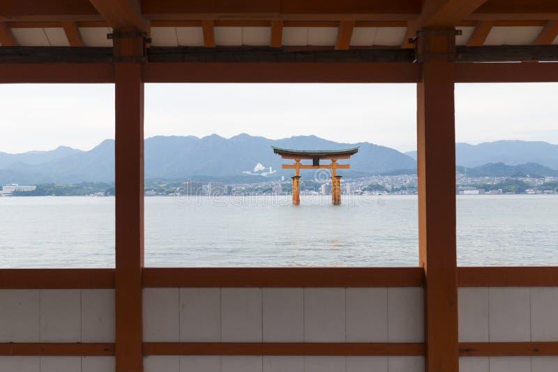 De Drijvende die Torii-poort door Itsukushima heiligdom in Miyajima, Japan wordt ontworpen stock foto's
