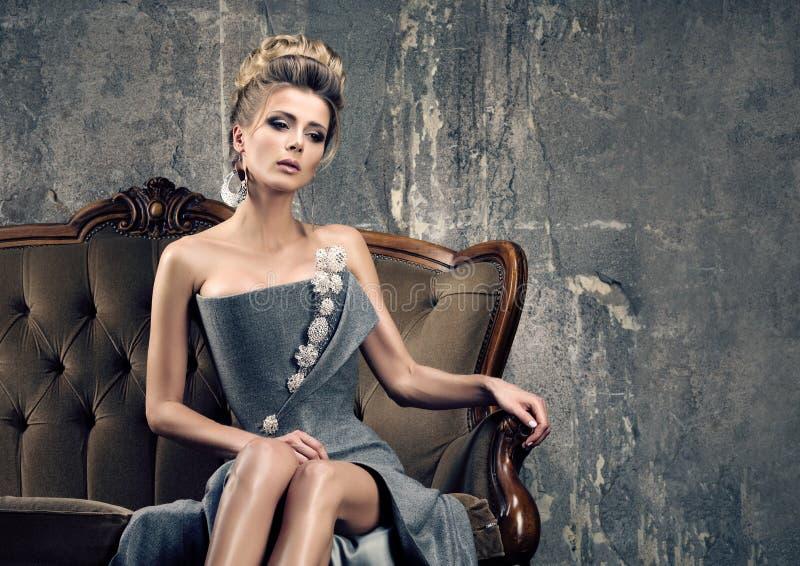 De droefheid van de partijtijd Eenzame mooie jonge vrouw in grijze avondjurkzitting stock foto