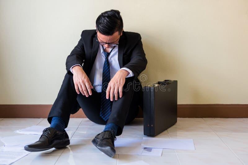 De droevige Aziatische zakenman zit op vloer stock afbeelding