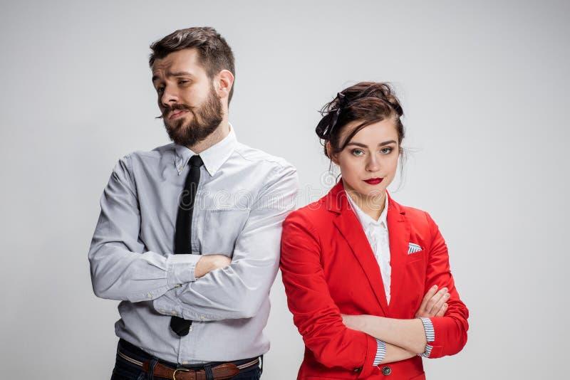 De droevige bedrijfsman en de vrouw die op een grijze achtergrond strijdig zijn stock foto