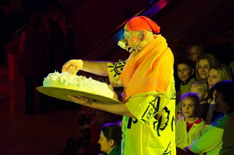 De droevige clown bevindt zich in publiek onder toeschouwers en houdt grote verjaardagscake stock afbeeldingen