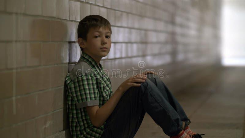 De droevige eenzame geslagen jongen zit op de vloer in een tunnel in diepe depressie bekijkend de camera, wacht niemand op royalty-vrije stock foto