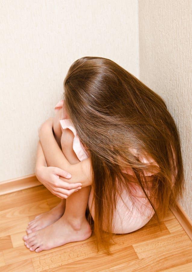 De droevige en gedeprimeerde gestrafte zitting van het meisjekind op de vloer dichtbij de muur royalty-vrije stock afbeelding
