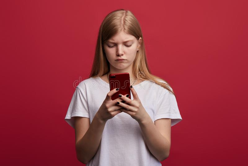 De droevige gedeprimeerde meisjestribunes gebruikt een smartphone royalty-vrije stock foto's