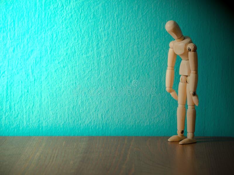 De droevige houten marionet is uitgeput en hopeloos Houten marionettentribune op de houten lijst de achtergrond is turkoois en ex stock foto