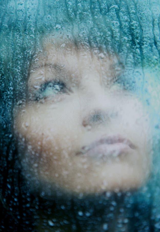 De droevige jonge vrouw en een regen dalen stock foto