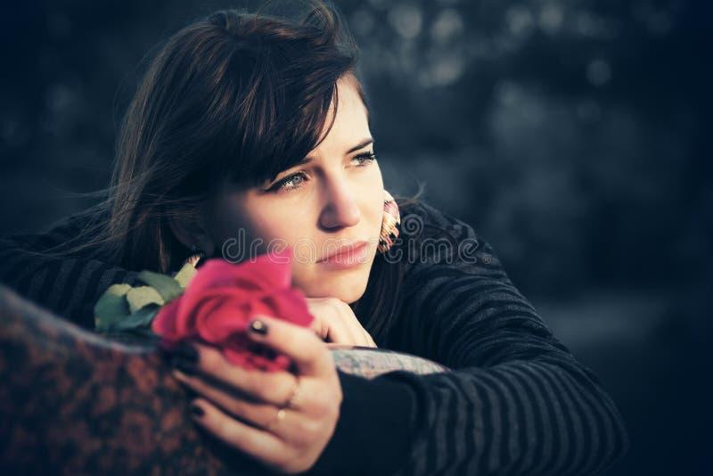 De droevige jonge vrouw met een rood nam toe royalty-vrije stock afbeeldingen