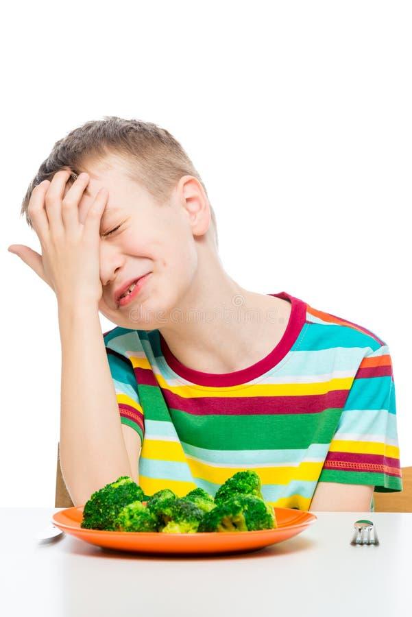 de droevige jongen wil geen broccoli, een portret met een plaat op een wit eten royalty-vrije stock afbeelding