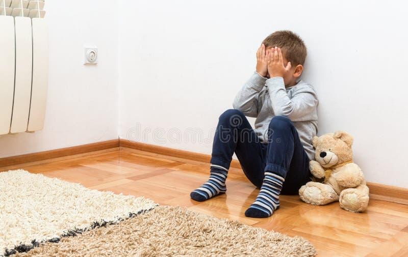 De droevige jongen zit op de vloer met zijn handen op zijn gezicht royalty-vrije stock fotografie
