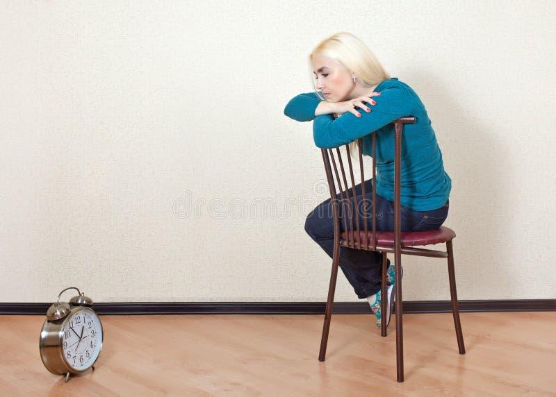 De droevige meisjeszitting op een stoel en bekijkt zijn horloge royalty-vrije stock afbeeldingen
