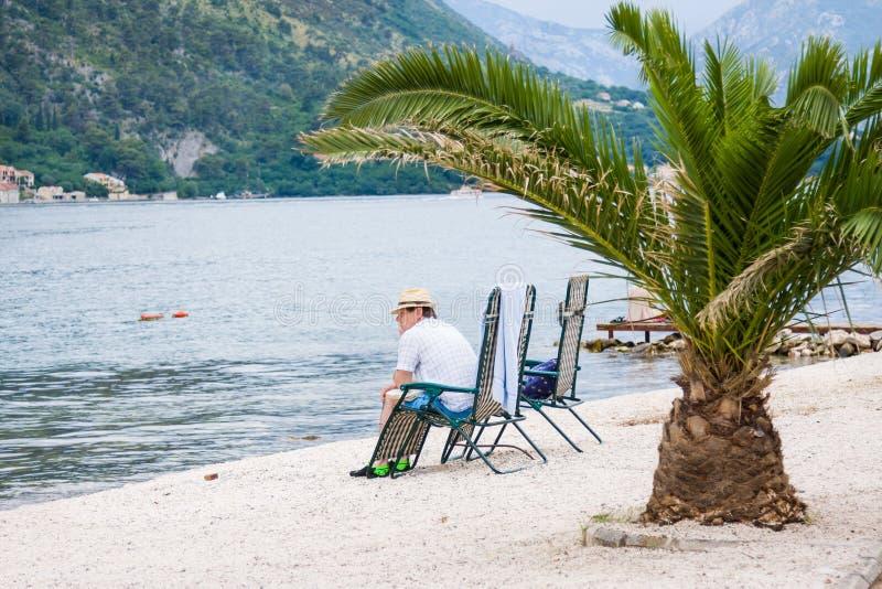 De droevige mens zit op het strand in onweersdag De Baai van Kotor, Montenegro stock foto's