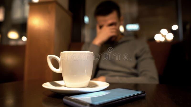 De droevige mensenzitting in koffie, sluitend gezicht, bericht van meisje verdeelt ongeveer stock foto's