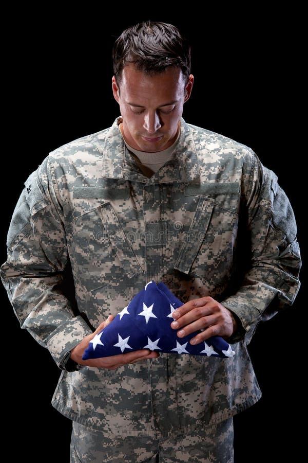 De droevige militair houdt een Vlag stock afbeeldingen