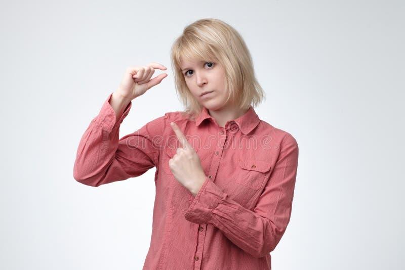 De droevige mooie positieve vrouw, gebaren toont de grootte van klein iets stock afbeelding