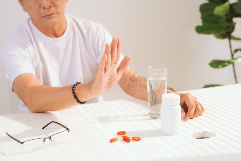 De droevige ongelukkige hogere mens wil niet aan het nemen van pillen stock foto's