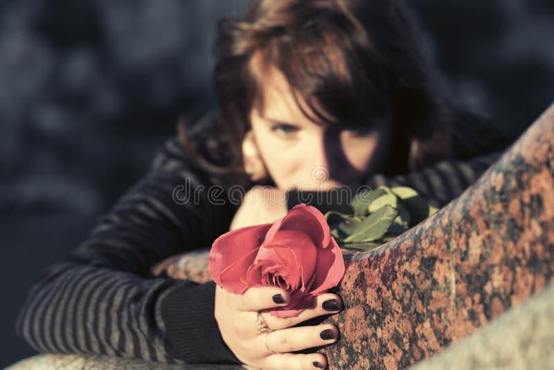 De droevige vrouw met een rood nam liggend op grafsteen toe stock afbeelding