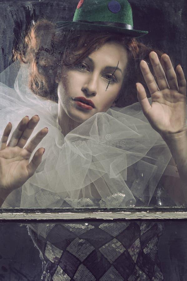 De droevige vrouw van de Pierrot achter het glas stock afbeeldingen