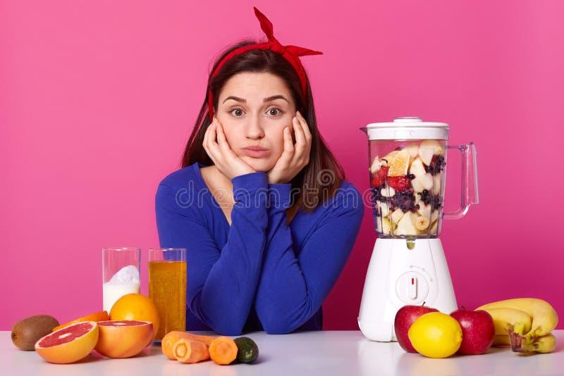 De droevige vrouw zit bij witte die lijst met mixer met vers fruit wordt gevuld, maakt smoothie voor ontbijt, raakt wangen en hou royalty-vrije stock fotografie